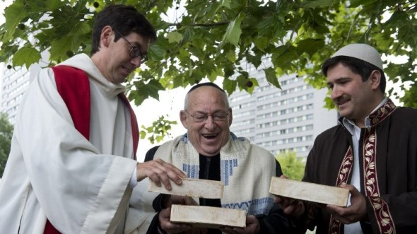 From L) German Pastor Gregor Hohberg, Israeli Rabbi Tovia Ben-Chorin and German-Turkish Imam Kadir Sanci hold three bricks as they pose for photographers in the vacant lot where they hope to build a multifaith prayer building, in Berlin June 3, 2014 (photo credit: AFP/JOHN MACDOUGALL)
