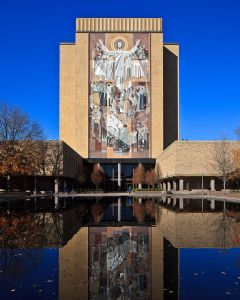 "The Word of Life is a large mural on the side of the Theodore Hesburgh Library depicting the resurrected Jesus. Designed by Millard Sheets, it was installed in 1964 as a gift of Mr. and Mrs. Howard V. Phalin. Stemming from the fashion in which Jesus' arms are raised and its visibility from Notre Dame Stadium, the mural has become popularly known as ""Touchdown Jesus."" Photo © 2012 by Mendaliv"